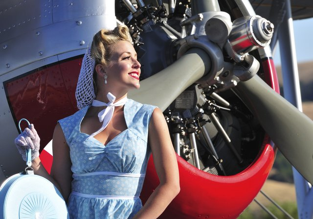 closeup of a classic 1940's lady in front of a vintage biplane